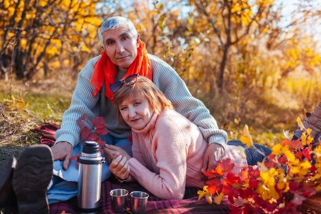 Senior couple having tea in autumn forest.
