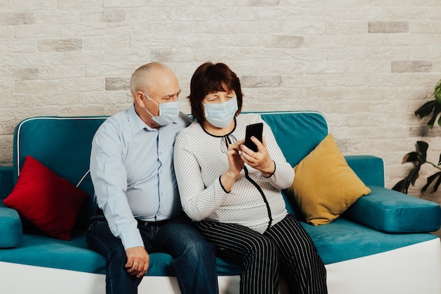 Senior couple having video call while wearing protective face masks due to coronavirus pandemic.