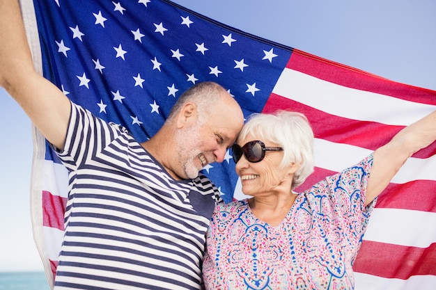 Senior couple holding american flag together