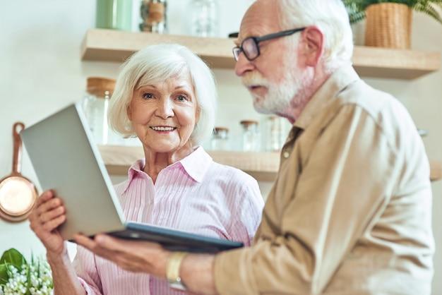 Senior couple holding computer on the kitchen