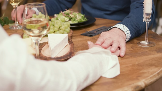 Senior couple holding hands during dinner in a restaurant. aged couple. happy couple in their sixties.