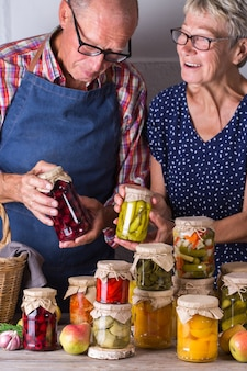 Senior couple holding in hands preserved food