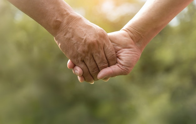 Senior couple holding hands together over green nature background.