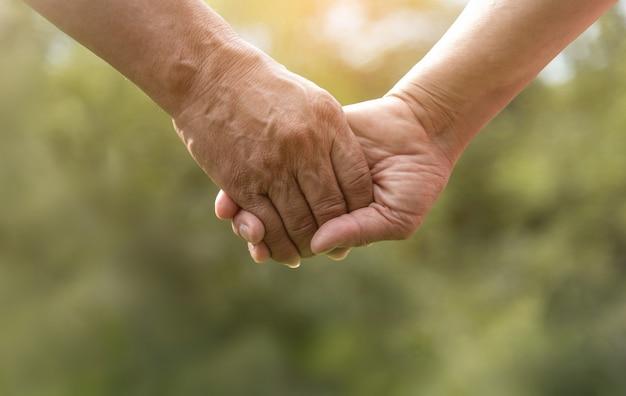 緑の自然の背景に一緒に手を繋いでいる年配のカップル。