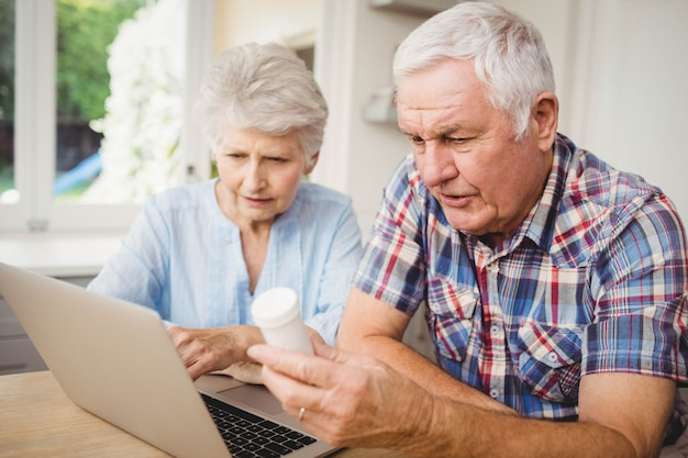 Senior couple holding a pill bottle and discussing while operating laptop