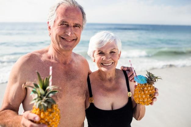 Senior couple holding pineapple cocktail on beach