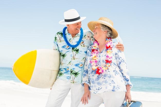 Senior couple holding surfboard