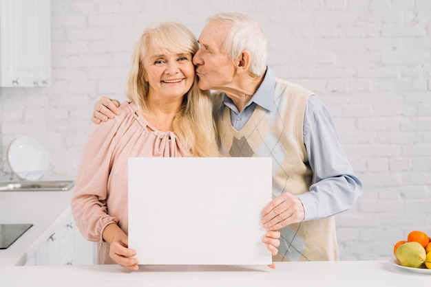 Senior couple holding template in kitchen