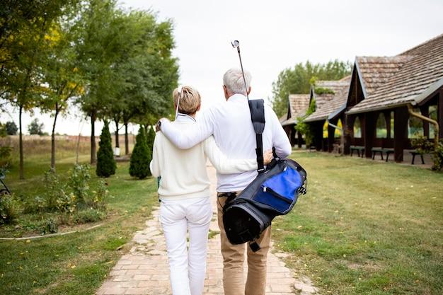 Старшие пары держатся вместе и наслаждаются отдыхом на пенсии, играя в гольф.