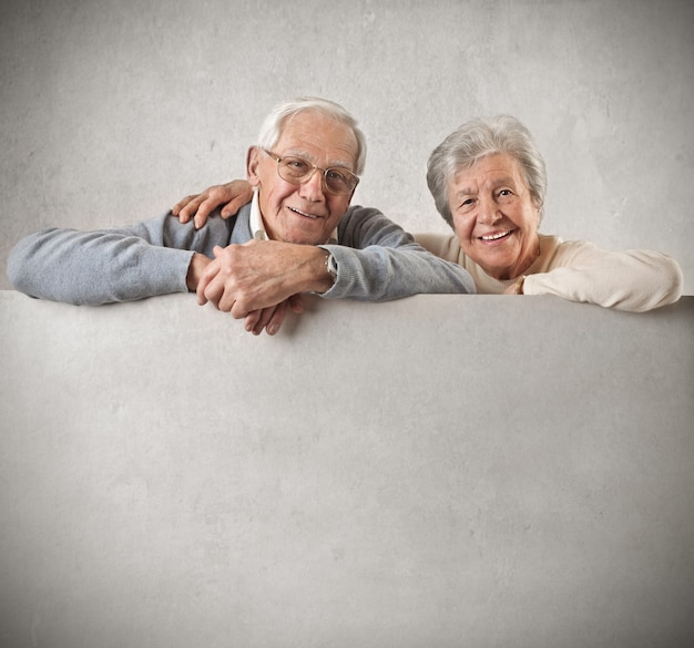 Senior couple holding with a blank board