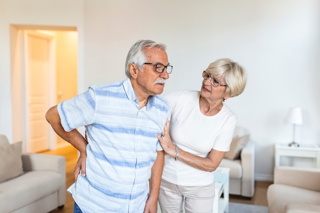 Senior couple at home.elderly man is having back pain and his lovley wife supports him.