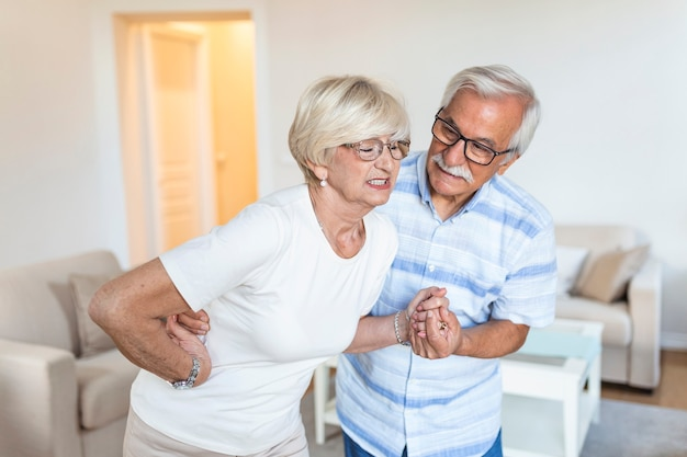 Senior couple at home. handsome old woman is having back pain and her attractive old husband supports her.