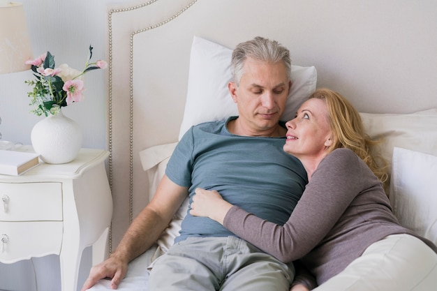 Senior couple hugging each other in bed