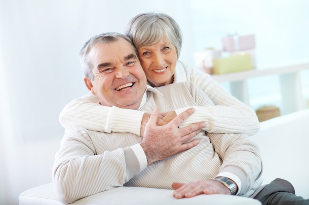 Senior couple hugging at home