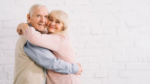 Пожилая пара обнимается Premium Фотографии