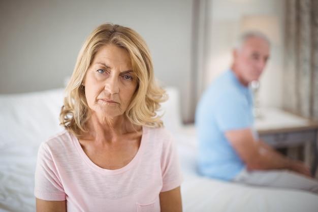 Пожилая пара игнорирует друг друга на кровати в спальне