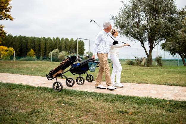 Пожилая пара в элегантной одежде и с клюшками для гольфа вместе идет на поле, чтобы поиграть в гольф.