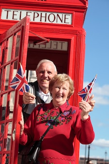 Старшие пары с красной телефонной коробки проведения британского флага в лондоне