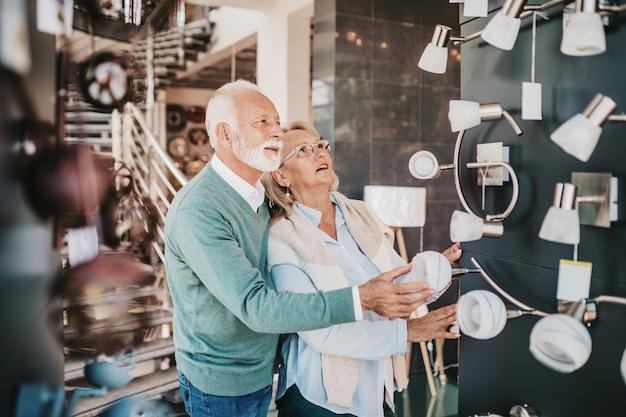 Пожилая пара в магазине домашнего освещения снимает люстра для своего дома