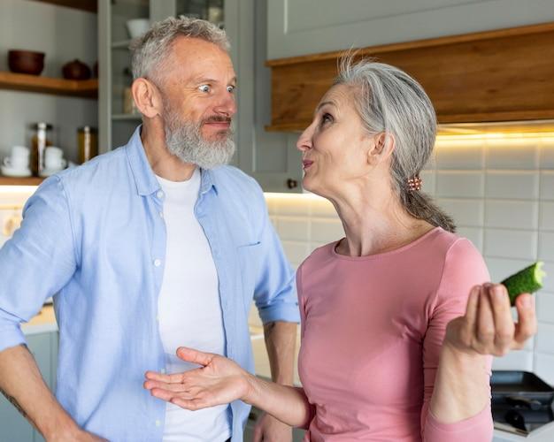 キッチンミディアムショットの年配のカップル