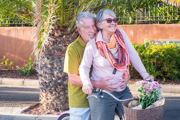 Старшие пары в любви отдыха на открытом воздухе вместе на велосипеде в винтажном стиле, улыбаясь и весело проводя время под солнцем отпуска. альтернативный способ остаться на пенсии, живя в тропическом месте