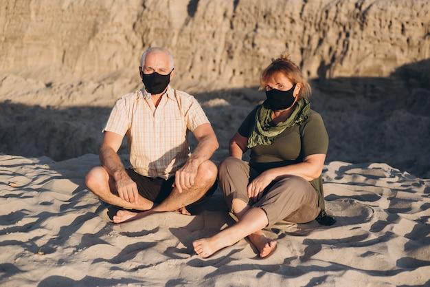 夏の自然の外でコロナウイルスから保護するための医療用マスクを着用したシニアカップル、コロナウイルス検疫