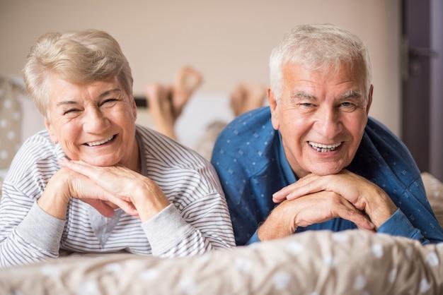 ベッドの上のパジャマで年配のカップル