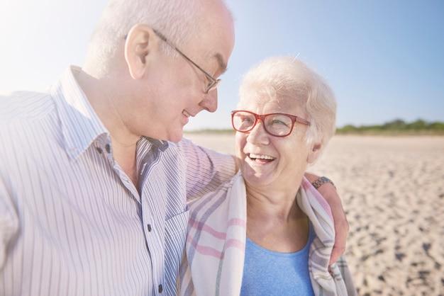 Старшая пара на пляже, пенсия и летние каникулы концепции