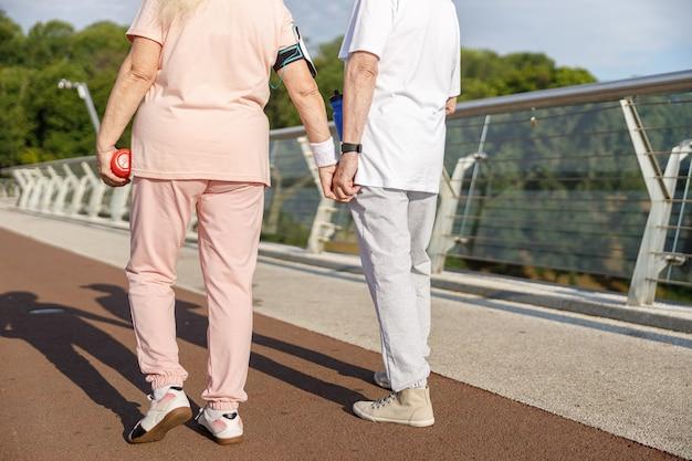 운동복을 입은 노인 부부는 일몰 시 인도교를 따라 손을 잡고 걷는다