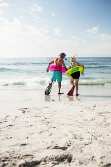 Senior couple in inflatable ring and flipper walking towards sea