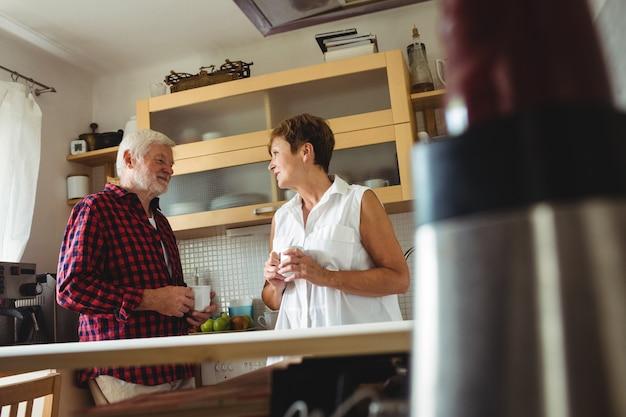 コーヒーを飲みながら相互作用する年配のカップル