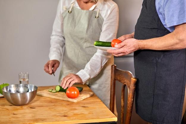 年配のカップルがキッチンで料理をしています。トリミングされた女性とハンサムな男性は家で一緒に時間を過ごしています。健康的なライフスタイルの概念