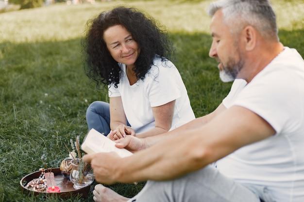 Старшая пара занимается йогой на открытом воздухе. растяжка в парке во время восхода солнца. брюнетка в белой футболке.