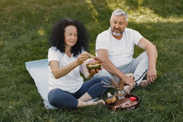 年配のカップルは屋外でヨガをやっています。日の出中に公園でストレッチします。白いtシャツのブルネット。
