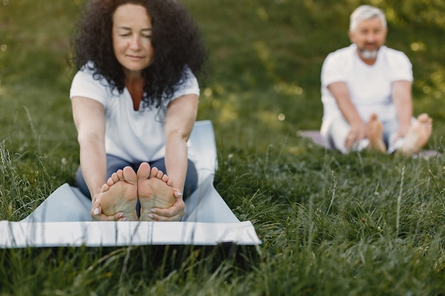 Senior couple is doing yoga outdoors. stretching in park during sunrise. brunette in a white t-shirt.