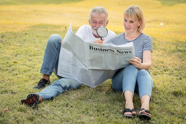 Пожилая пара сидит, смотрит газеты на лужайке.