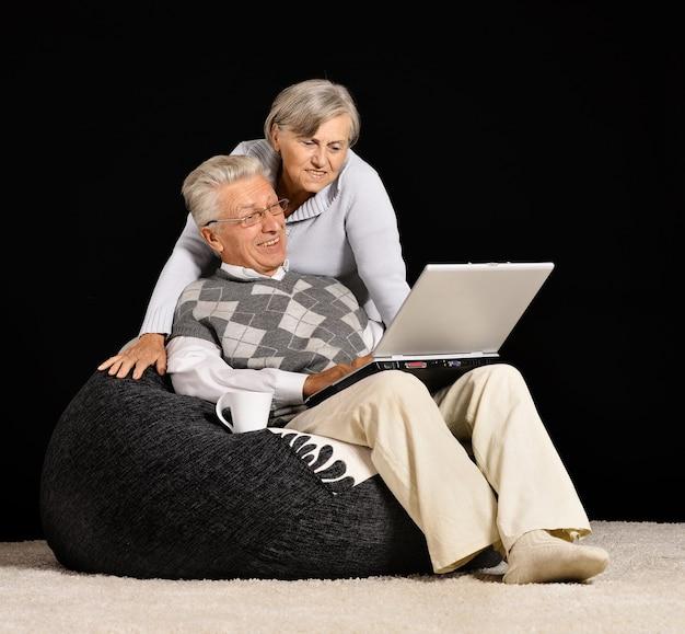 수석 부부는 검은 배경에 앉아 노트북으로 작업하고 있습니다