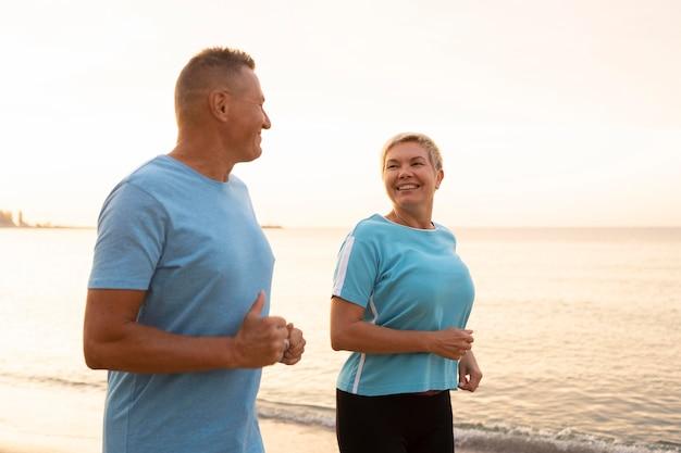 コピースペースと一緒にビーチでジョギングシニアカップル
