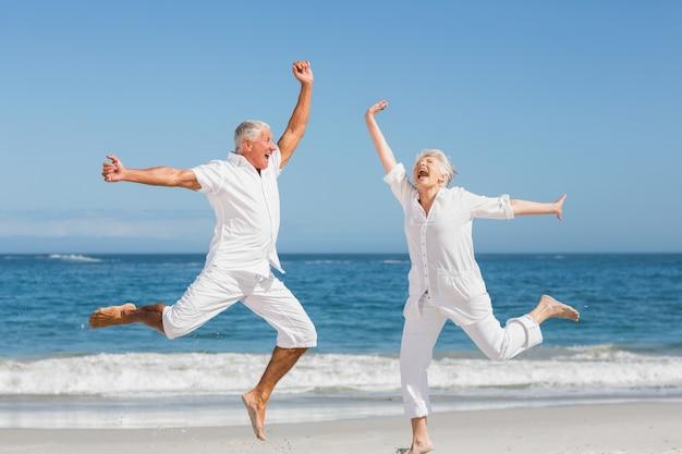 ビーチでジャンプする年配のカップル