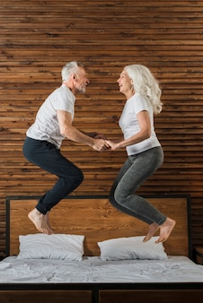Senior couple jumping in bed