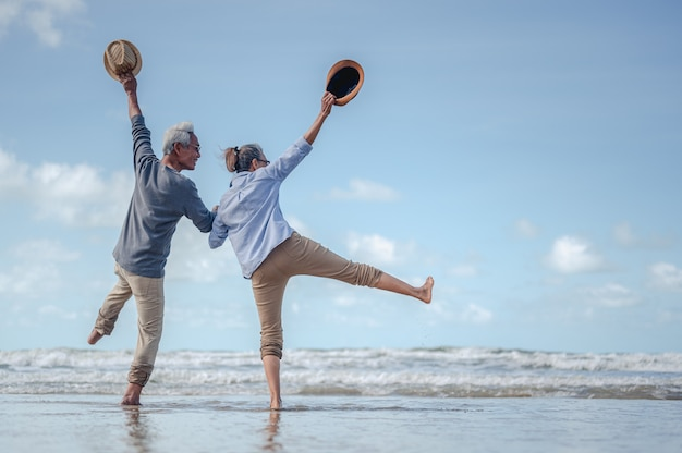 Senior couple jumping in hand in hand on the beach at sunny day, plan life insurance with the concept of happy retirement.