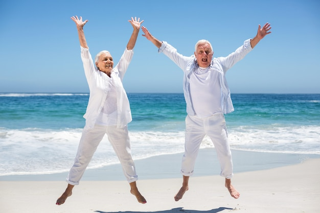 Senior couple jumping with raised arms