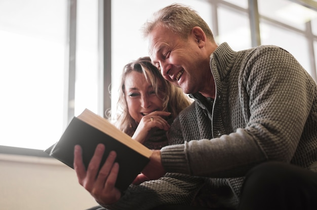Senior couple laughing at book