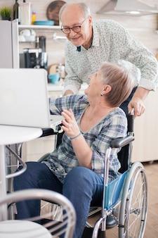 キッチンでタブレットコンピューターを使用して孫とのビデオ通話中に笑っている年配のカップル。現代のコミュニケーション技術を使用して麻痺した障害のある老婆。