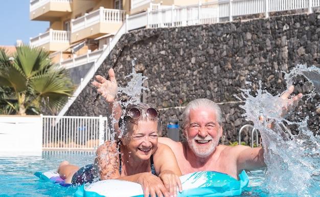 매트리스를 가지고 노는 수영장에서 웃고 있는 노부부 행복한 은퇴한 사람들은 즐거운 시간을 보낸다
