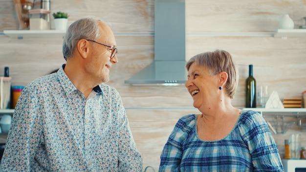 キッチンでカメラを見ながら笑っている年配のカップル。陽気な老人と女性の笑顔と笑い。生活を楽しんでいる居心地の良い家で幸せな高齢者退職者