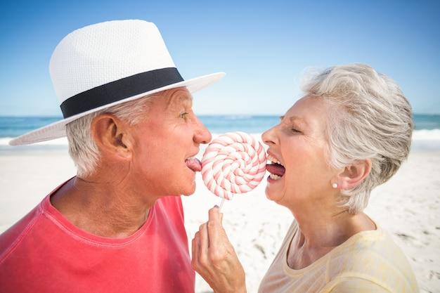 ロリポップをなめる年配のカップル