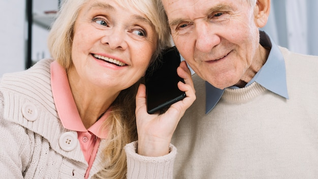 Senior couple listening to smartphone