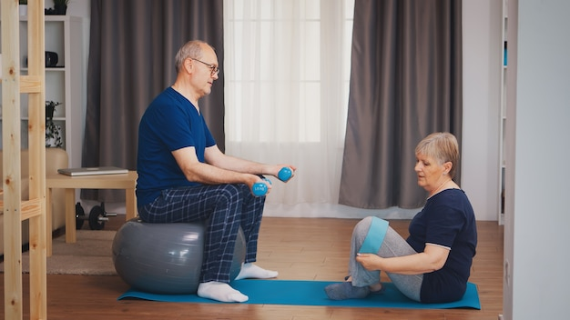 Senior couple in living room doing physical training on yoga mat and stability ball. old person healthy lifestyle exercise at home, workout and training, sport activity at home