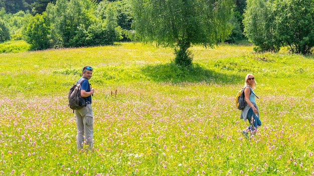 Senior couple looked back on the hiking at bright green alley. beautiful family travel